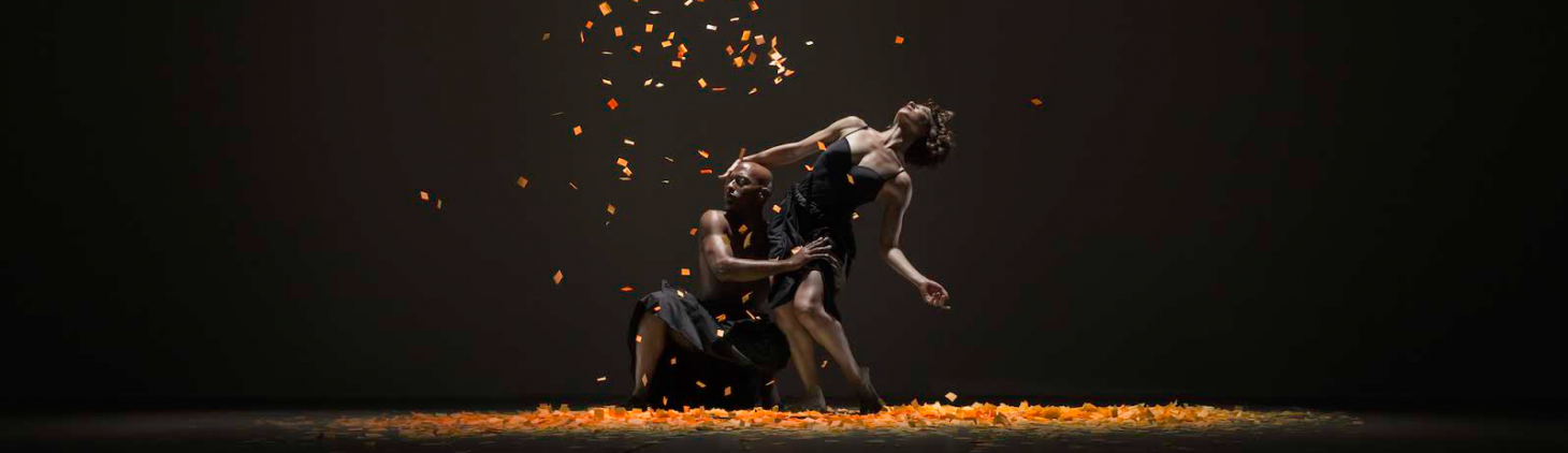 An image of two dancers, one crouched down next to the other dancer looking up towards the light while orange confetti falls